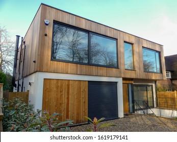 Chorleywood, Hertfordshire, England, UK - January 18th 2020: Modern two storey flat roofed house, clad with external cedar wood