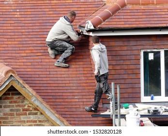 Chorleywood, Hertfordshire, England, UK - October 16th 2019: Polish workmen fitting gutter to fascia board of new house roof dormer
