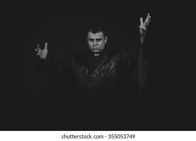 Chorno white photography priest on a dark background. Emotional Photos religious rights. Photo for religious magazines and websites.