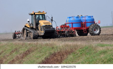 """Chortkiv - Ternopil - Ukraine - April 10, 2018. On a spring field a powerful tractor CAT Challenger agrofirma """"Dzvin"""" prepares soil for sowing and simultaneously brings water ammonia"""