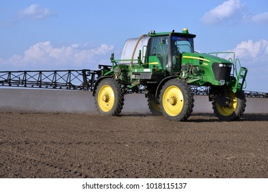 """Chortkiv - Ternopil - Ukraine - April 5, 2017. On the self-propelled sprayer John Deer works with GPS navigation that makes herbicides on the fields of the agrarian enterprise """"Dzvin"""" in Ukraine"""