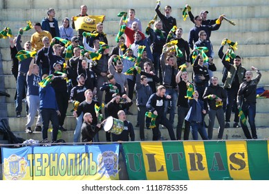 """Chortkiv - Ternopil - Ukraine - April 8, 2017. At the podium fans of the football club """"Nyva"""" Ternopil support their team while playing with """"Crystal"""" in the regional championship"""