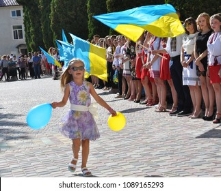 Chortkiv - Ternopil - Ukraine - August 31, 2017. A little girl running with a ball against the background of the state flags of Ukraine during the celebrations at the State Pedagogical College