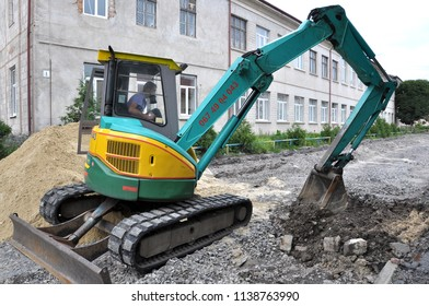 Chortkiv - Ternopil - Ukraine - July 18, 2018. Mini excavatorwith rubber caterpillar works on road repair in the city of Chortkiv.