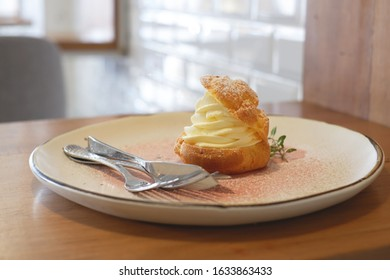 chou à la crème on white plate with fork and spoon on wooden desk