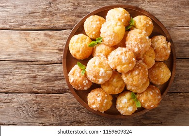 Chouquettes French Cream Puffs dessert is decorated with pearl sugar and mint closeup on a table. horizontal top view from above
