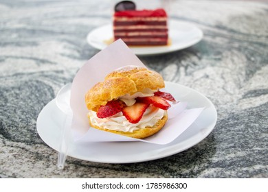 Choux cream, profiteroles with cream, and strawberry on white plate
