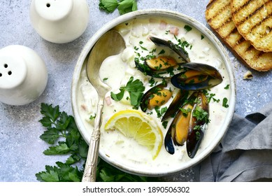 Chowder - delicious fish soup with mussels in a bowl on light grey slate, stone or concrete background. Top view with copy space.