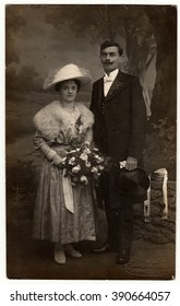 CHRASTAVA (KRATZAU), THE CZECHOSLOVAK  REPUBLIC - CIRCA 1920s: Vintage photo of newlyweds. Bride wears a furry shawl and  white wide- brimmed hat with netting. Groom wears posh clothing, white bow-tie