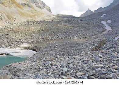The Chriegalp Pass on the border between Switzerland and Italy with a glacial lake and small icebergs breaking away from the melting glacier as the climate warms