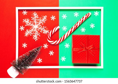 Chrismas composition with present box, decorative fir tree, lollipop and snowflakes on red and green background with white frame. Winter holiday concept. Top view. Flat lay