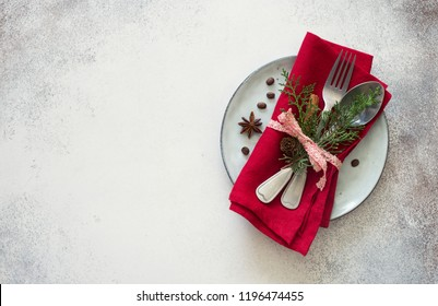 Chrismas table place setting. Tableware, evergreen twigs, cone and spice. New Year food concept