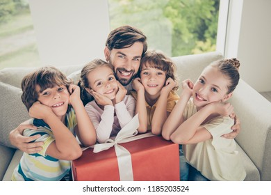 Christams, xmas, new, year, winter, holiday concept. Portrait of family one parent and fout kids. Dad sit on comfort couch, hug adorable kids, holds on his knees big red package in modern light flat
