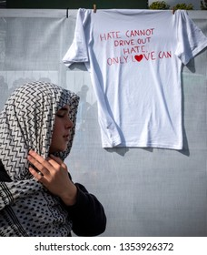 Christchurch, Canterbury, New Zealand, March 29 2019: A young woman places a t-shirt on a security barrier during today's remembrance service for victims of the March 15 Christchurch Mosque Shootings