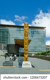CHRISTCHURCH, NEW ZEALAND – DECEMBER 14, 2017: A traditional Maori carved wooden sculpture greets visitors to the refurbished City Council Building with the words,Te Pou Herenga Waka.