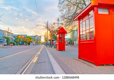 CHRISTCHURCH NEW ZEALAND - OCTOBER 10; Bright red telephone booths along street with tramlines at dawn when street lights on Worcester Boulevard October 10 2018 Christchurch New Zealand