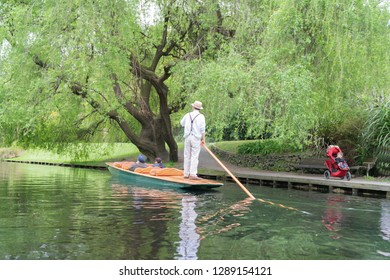 CHRISTCHURCH, NEW ZEALAND - OCTOBER 10; Punting on the Avon River tourists being punted under riverside weeping willow tree October 10 2018 Christchurch New Zealand