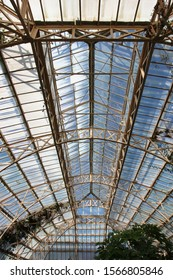 Christchurch, New Zealand - October 16, 2015: The large victorian Cuningham House glasshouse conservatory of the Christchurch Botanic Gardens. Morning sunlight is entering the glass roof.