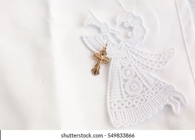 Christening accessories: little golden cross on embroidery of angel