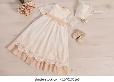 christening baby dress. Close-up of a cute newborn baby dress. Stylish embroidered white dress. Concept childhood education and fashion