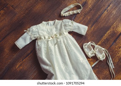 christening baby dress and shoes. Close-up of a cute newborn. small shoes and a dress on a background of wood. Concept childhood education and fashion.