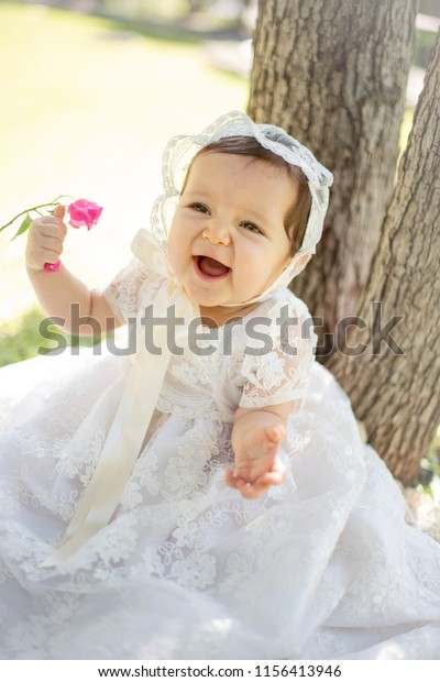 Christening baby in her dress smiling. Monterrey, Mexico. August 9, 2018.