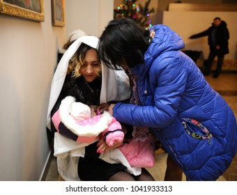 Christening for baby in a rural church. Mother and her kinswoman put clothes on baby after baptizing. January 7, 2018. Bucha village, Ukraine