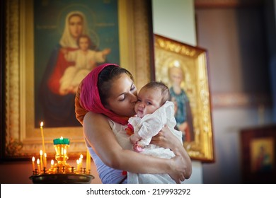 Christening ceremony. Family celebrating baptism in Orthodox Church. A young beautiful mother in the pink headscarf holding  her new-born baby in her arms and kissing the girl.