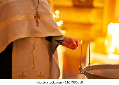 Christening ceremony in the Orthodox church, priest lighting candles at children baptismal font, close up