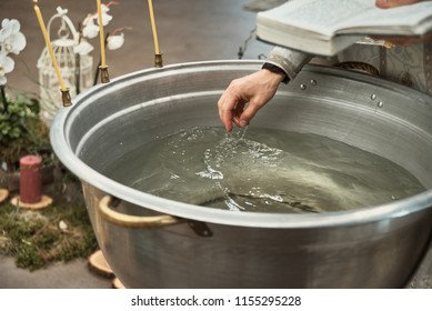 Christening in the church, Details in the orthodox christian church. Big bowl of water for the baptism of a baby with wax candles. Orthodox rite of blessing water on the feast of baptism