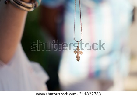 Christening golden cross on the lace. Horizontal photo