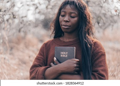 Christian afro girl holds bible in her hands. Reading the Holy Bible. Concept for faith, spirituality and religion.