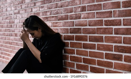 Christian Asian woman is sitting against a wall, feeling sad, holding a cross and praying to God.