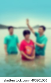 christian baptism in the sea blur background