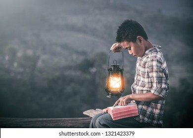christian Boy holding oil lamp and reading bible, christian concept