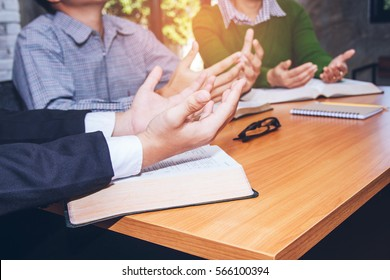 Christian business man and women reading bible and praying to God in the office, raise hands up on burred open bible on wooden table, Christian concept or background