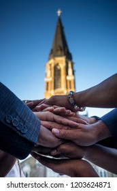 Christian charity organization.  Hands of people infront of a church.  Helping hands.
