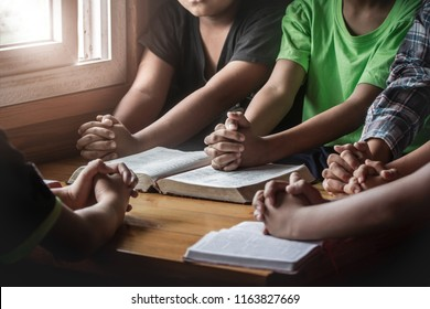christian children group praying together around wooden table with open bible page in home room, prayer meeting concept