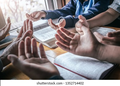 Christian children group praying together around wooden table with open bible page at home, prayer meeting concept.