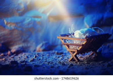 Christian Christmas concept. Birth of Jesus Christ. Wooden manger in cave background. Banner. Nativity scene symbol. Jesus is reason for season. Salvation, Messiah, Emmanuel, God with us, hope.