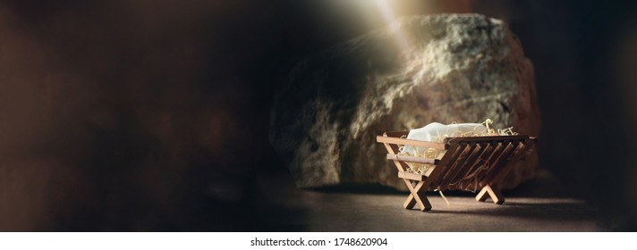 Christian Christmas concept. Birth of Jesus Christ. Wooden manger in cave background. Copy space. Nativity scene symbol. Jesus is reason for season. Salvation, Messiah, Emmanuel, God with us,