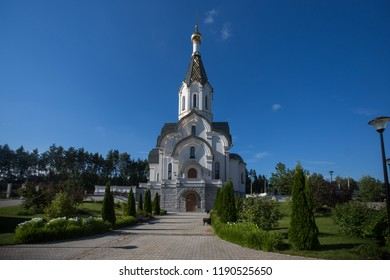 Christian Church in modern landscape of European city, beautiful well-groomed area around religious building, Sunny day and bright blue sky, appeal to God, faith in highest forces, atheism or prayer