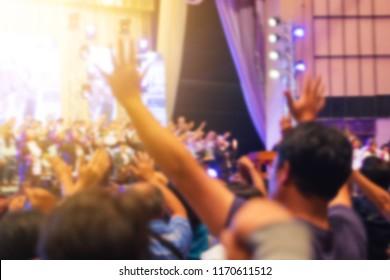 ฺBlurred of Christian congregation worship God together in big Concert hall with music stage light effected. christian background with copy space.