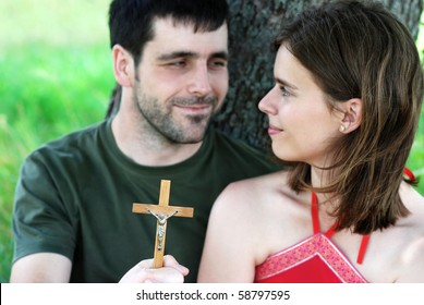 Christian couple is praying in the nature.
