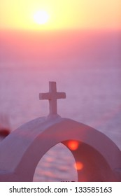 christian cross of a church on santorini at sunset