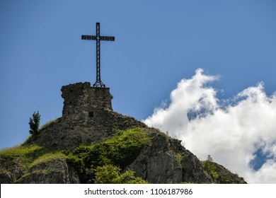 Christian cross erected on a rock against cloudy sky. Shot in Pennabilli, Italy