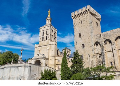 Christian cross in front of Cathedral and Papal palace in Avignon in a beautiful summer day, France