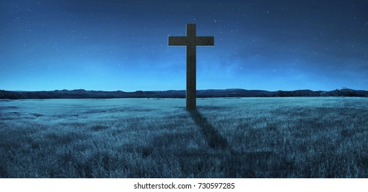 Christian cross in the middle of meadow. Religion concept