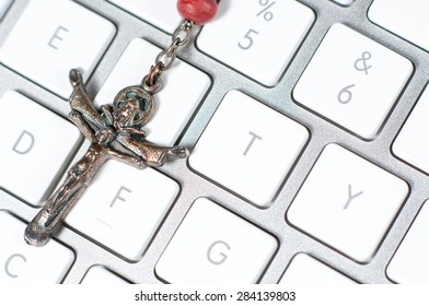 Christian cross necklace on a white modern computer keyboard.