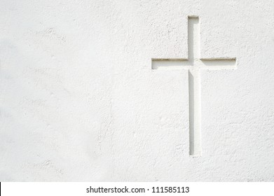 Christian cross on building wall. All white and space for text on the left part of the picture.